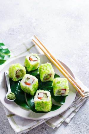 sushi roll with green caviar on a plate with chopsticks on stone background